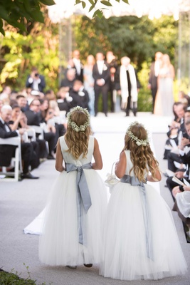 Back of flower girls walking down aisle with grey satin ribbon and baby's breath flower crowns
