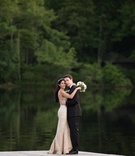 groom in Ermenegildo Zegna hugs bride in mark ingram blush wedding dress in front of lake