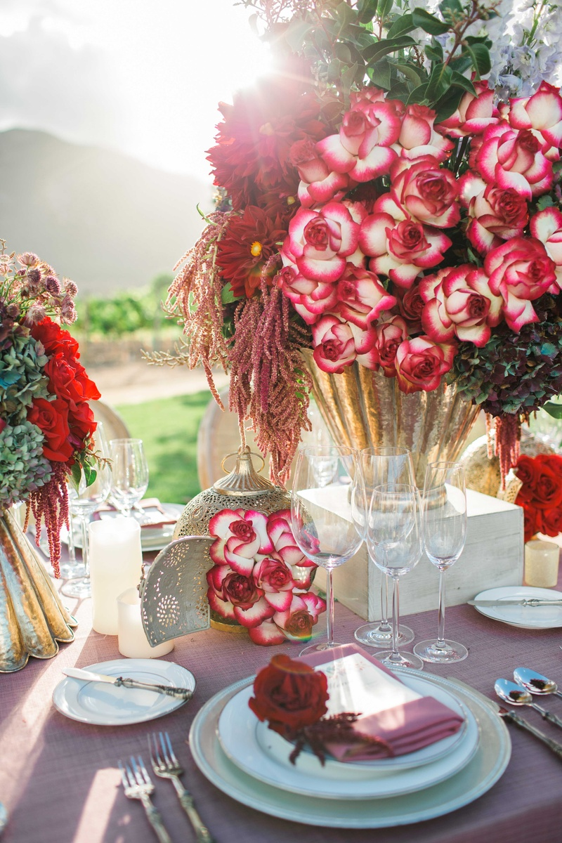 red and dark purple flowers floral arrangements in gold vases on pink table linens and lanterns