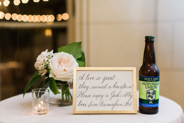 Wedding calligraphy sign gold frame next to Jack's Abby beer bottle craft beer wedding reception