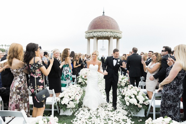 bride and groom hold hands walking up aisle friends clapping resort at pelican hill flowers by cina