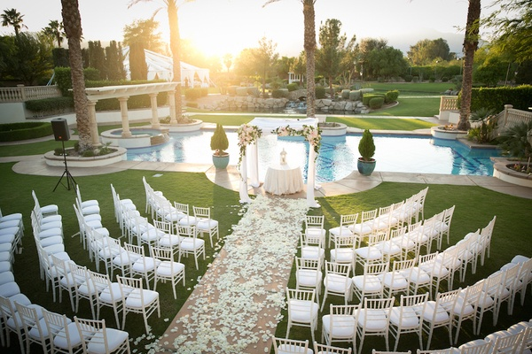 Rows of chairs with view of chuppah and pool