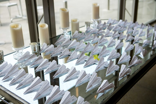 reception escort cards in the form of paper airplanes to honor grooms profession as a pilot