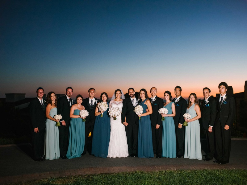 Bridesmaids in mismatched blue bridesmaid dresses with groomsmen in suits at sunset Terranea resort
