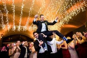 Groomsmen guests lifting groom during hora jewish wedding reception twinkle lights hanging ceiling