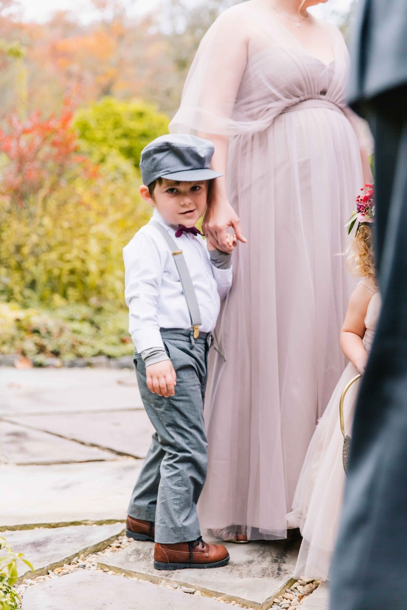 little boy in gray pants and suspenders and hat with purple bow tie and brown shoes