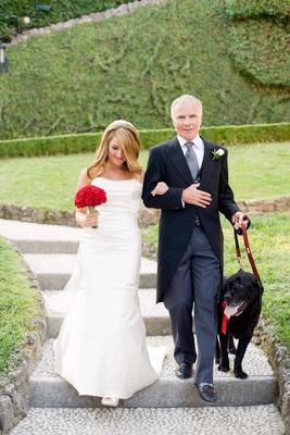 Bride and groom walking black dog down aisle