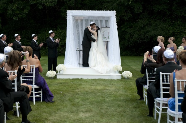 Simple alfresco ceremony with white chuppah