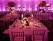 Purple and pink lighting at large indoor wedding reception