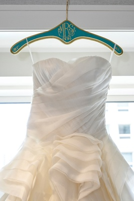 a-line wedding dress hung up on custom blue and yellow hanger with mrs in calligraphy