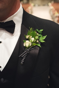 Wedding boutonniere of white flowers and leaves tied with black ribbon