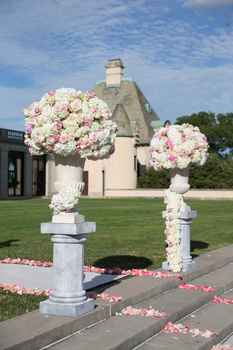 White hydrangea pink rose flower arrangement on column riser aisle with pink flower petals