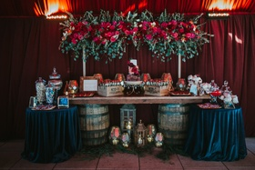 wedding sweets table, dark moody colors, wine barrel as table support