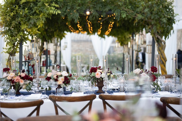 wedding reception under canopy of greenery with twinkle lights, vineyard chairs, floral centerpieces