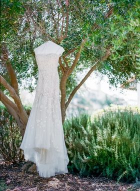 monique lhuillier wedding dress with spaghetti straps and floral embellishments