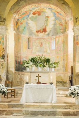 wedding ceremony stone steps and altar fresco paintings abbey chapel greenery white flowers cross