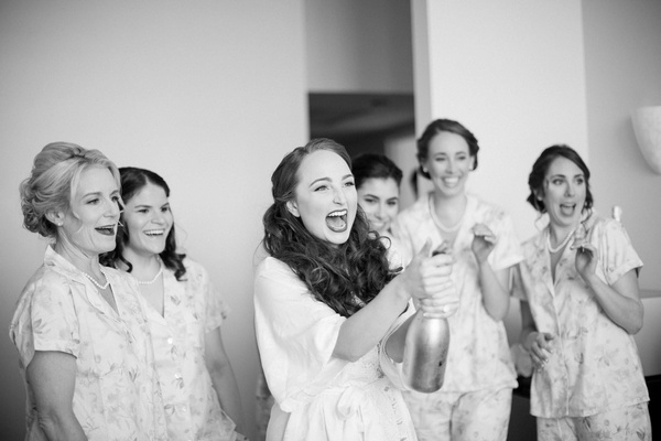 black and white photo of bride popping champagne bridesmaids getting ready wedding fun