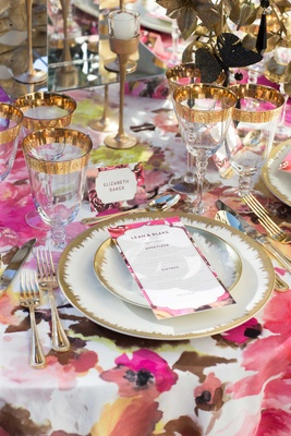 gold leaf china charger plates wine glasses flatware silverware with invitations candles pink linen