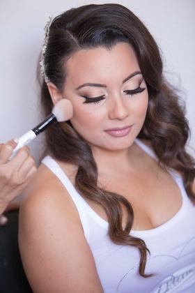 Bride getting makeup done at wedding natural curled hair headpiece makeup brush
