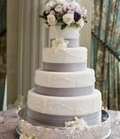 White cake with ribbon band and fresh flowers on top