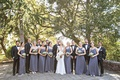 Wedding guests bridesmaids in mismatched purple grey gown groomsmen in tuxedos