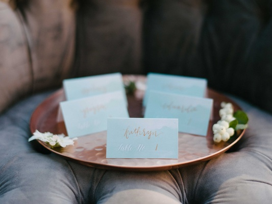 small blue escort cards with rose gold calligraphy on a rose gold serving platter on a brown chair