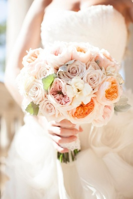 Bride carrying garden roses and gardenias