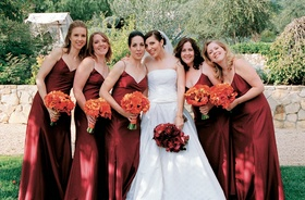 bridesmaids in long red spaghetti strap dresses and orange bouquets