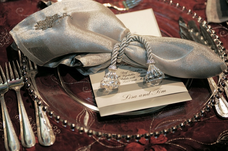Reception place setting of clear charger with a silver beaded rim topped with a silver napkin