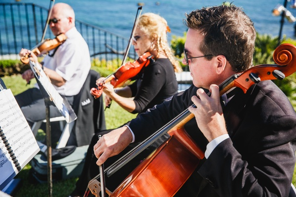 Musicians sit near the ocean adding live music the the ceremony.