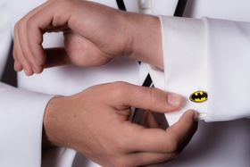 Wedding guest in white tuxedo jacket wears batman logo cuff link with white shirt