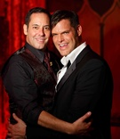 Matthew Christopher, couture wedding gown designer, in a black tuxedo with his groom