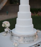 Wedding cake with white fondant, lace, quilted design, and pearls on a silver stand