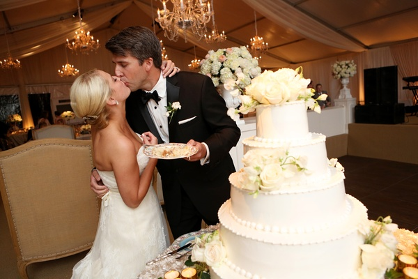 bride and groom kissing beside wedding cake, cake eating tradition