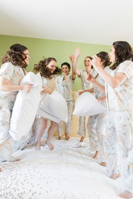 bride bridesmaids jump on bed pillow fight wedding florida getting ready matching pjs outfits