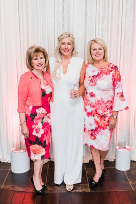 bridal shower bride-to-be in white monique lhuillier jumpsuit with hosts in pink floral dresses.