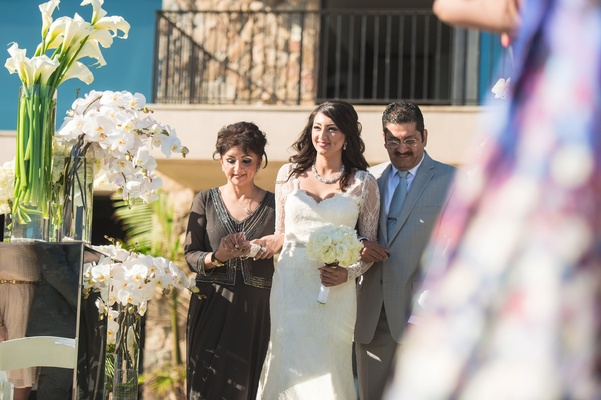 Bride and parents walk down aisle lined with white calla lilies and orchids.