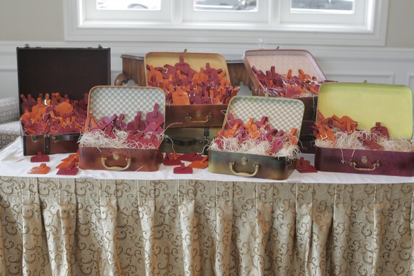 Wedding favors of luggage tags arranged in suitcases