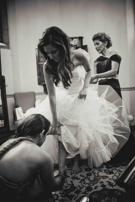 Black and white photo of bride getting dressed with mom and bridesmaid