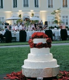 White wedding cake embellished with red roses