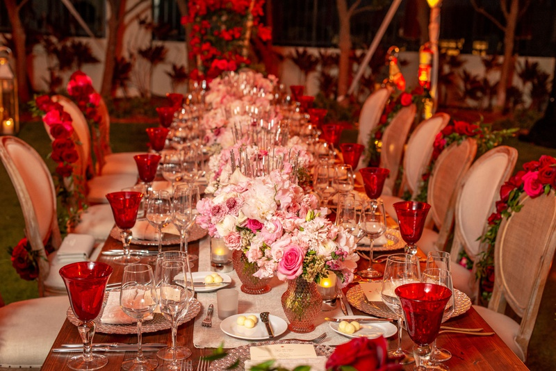 wedding reception long wood table pink flower centerpiece red goblets roses