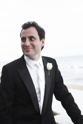 Groom in front of beach with white boutonniere
