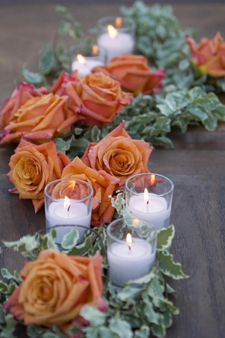 Orange roses with greenery and small white candles
