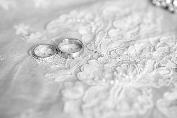 Black and white photo of Tiffany & Co. wedding rings on lace