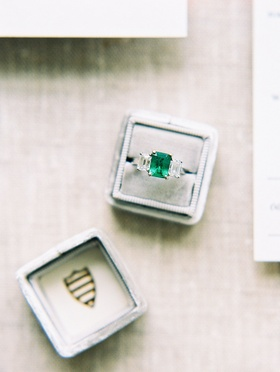 Wedding ring in grey box with crest three stone ring with emerald center stone two side stones
