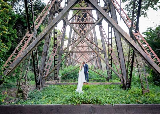 wedding photo portrait under bridge navy blue suit white dress santa barbara california forest venue