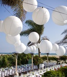 White sphere paper lanterns above beach wedding