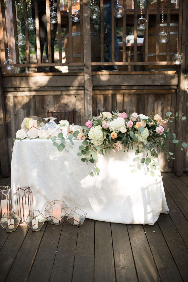 wedding reception wood deck with sweetheart table terrarium gold geometric candle holders eucalyptus