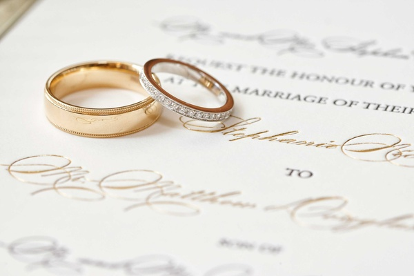 Gold polished men's wedding band ring and women's gold ring with diamond pave details on invitation