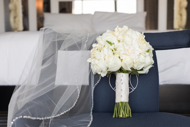 traditional white flower bridal bouquet next to veil with crystal border